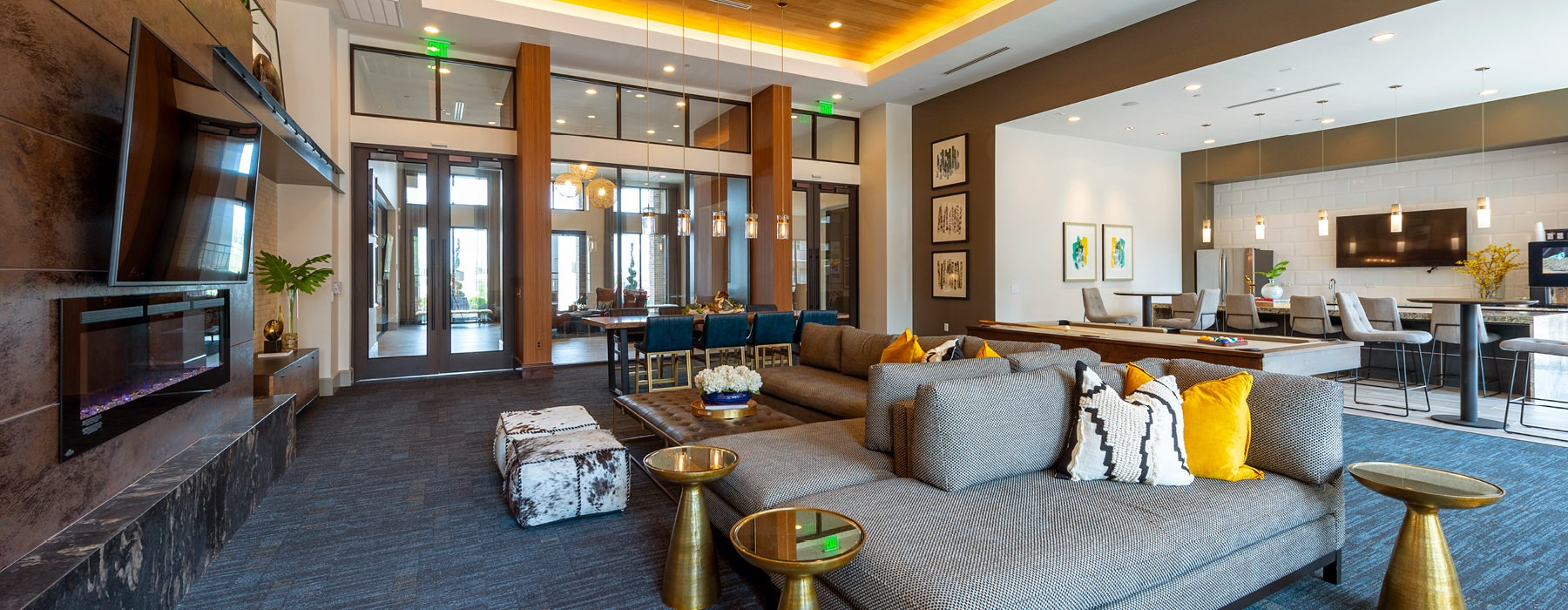 roomy clubhouse with large couch in front of fireplace and tv
